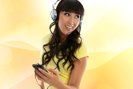 Girl enjoying music through headphones on a portable player.  Yellow and soft orange swril background Stock Photo - 10541419