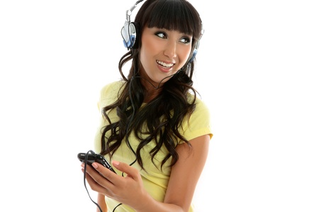 A young woman having fun is enjoying music through a portable mp3 player or similar.  White background. photo