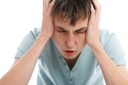 remorse: A teen boy showing signs of a headache, migrain or stress.