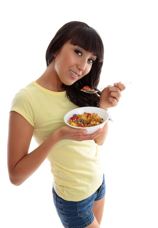 A young smiling woman eating a nutritious healthy breakfast.  White background photo