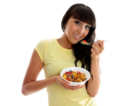 A beautiful smiling woman eating a healthy breakfast of cereals, nuts and fruit.  White background. photo