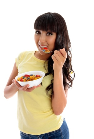 A young happy woman enjoying eating delicious cereal.  White background. photo