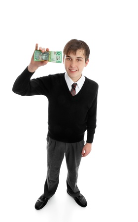 Teen school boy holding a wad of cash  up in one hand.  photo