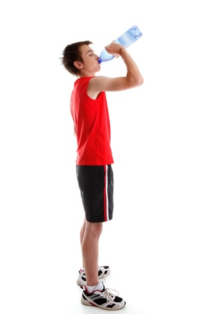 A teenage boy dressed in sports wear is drinking water from a bottle.  White background. photo