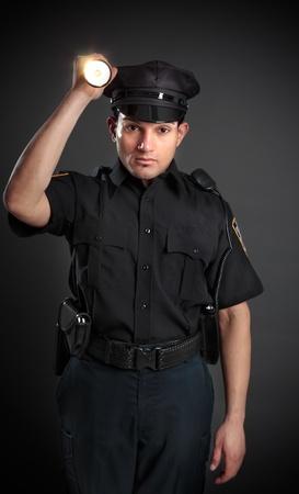 guarda de seguridad: Un polic�a, polic�a o guardia de seguridad la noche la luz de una antorcha linterna para investigar o buscar. Foto de archivo