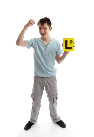 l first: A teen boy holding his L plates (learner driving plates) and showing a fist of success.  White background. Or, plates maybe replaced with your brochure or other object.