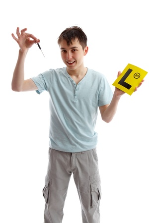 l first: A smiling teenager holding car key and L learner plates.  White background.