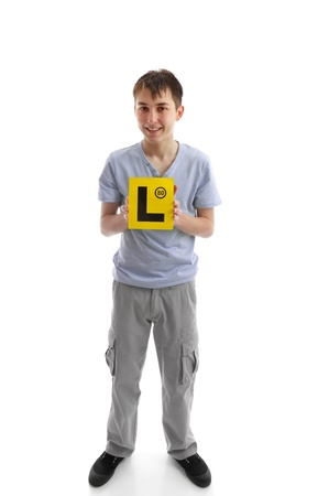 l first: A teenage boy holds  L learner plate and smiling. Stock Photo