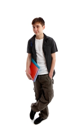 A high school or college student stands in casual clothes and carrying some books under one arn.  White background.