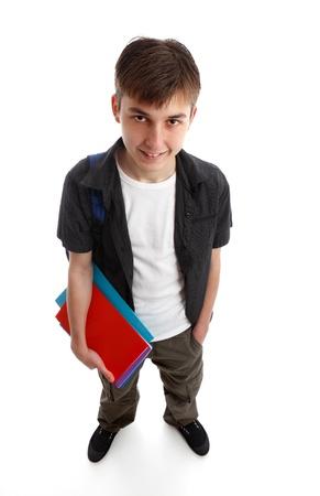 Un estudiante adolescente masculino de pie en ropa casual y la celebración de algunos libros en una mano. Fondo blanco.