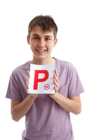 provisional: Un adolescente con un cartel P placa magn�tica para el coche. Licencia provisional. Fondo blanco.