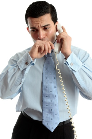 A very worried or anxious businessman or other professional on the phone.  White background. Banque d'images