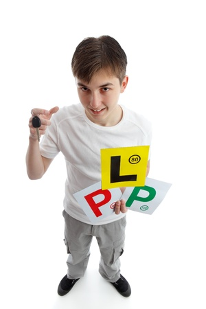 provisional: Full length teenager looking up.  He is holding a car key and various licence plate signs for learner drivers.  White background. Stock Photo