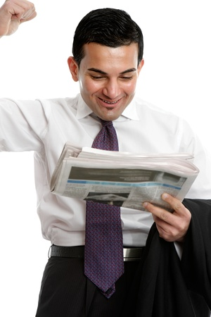 A businessman reading the newspaper, punches the air with a fist of excitement.  Please note newspaper editorial has been blurred beyond comprehension.  White background. photo