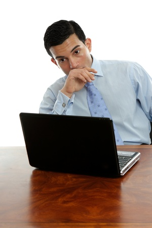 Man sitting at his desk with laptop thinking deeply photo