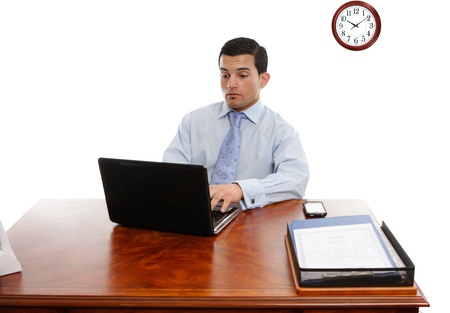 Businessman sitting at his desk working typing on a laptop computer Stock Photo - 13496898