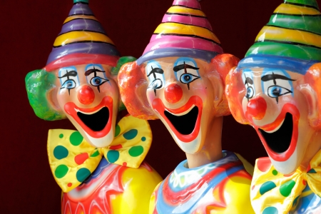 clowns: A row of sideshow carnival game clowns with mouths open.  Focus to middle clown. Stock Photo
