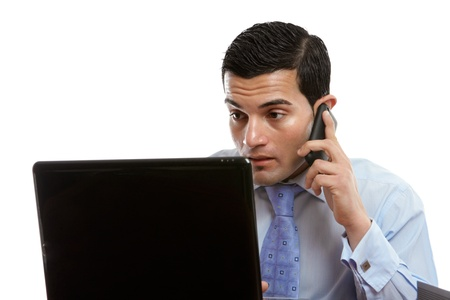 A man sitting at his computer is making or receiving a telephone call. Stock Photo - 13605897