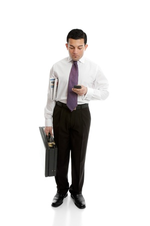 A businessman either making a phone call or reading or sending a sms text message,  Stock Photo - 13635571