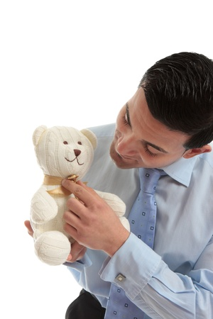 Salesman holding a toy teddy bear and adjusting its ribbon bow. Stock Photo - 13736559