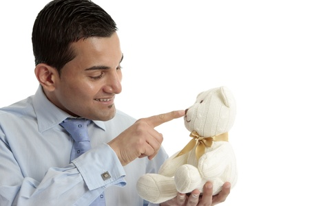 Smiling businessman or salesman touching the nose of a cream wool knitted teddy bear. Stock Photo - 13736558