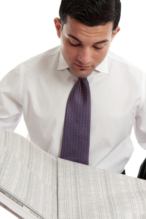 An investment banker, or stockbroker reading the finance sharemarket pages of the newspaper. Stock Photo - 13843160