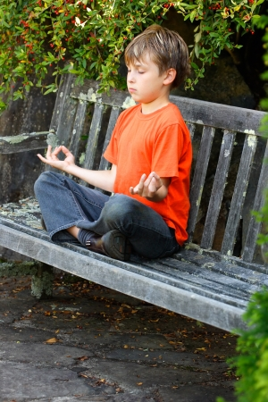 A boy sitting cross legged in yoga zen meditation photo
