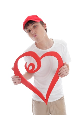 puckered: A teenage boy holding a red love heart with lips puckered up kissing.  White background.