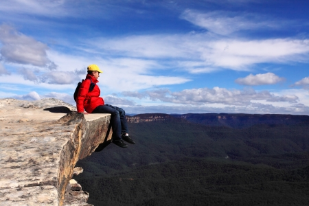 admires: Sitting on Top of the World - hiker rests and admires views of Blue Mountains on a beautiful sunny day.  Selective focus.
