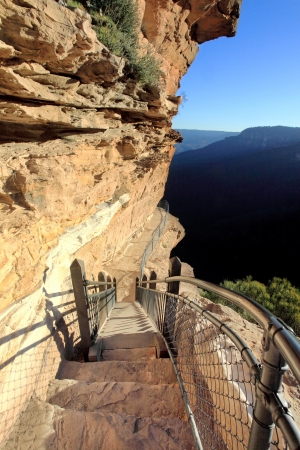 steep cliff: Awe inspiring National Pass trail clings impossibly to the sheer cliff face, Blue Mountains, Australia   The trail is rated hard, but takes you through breathtaking scenery and waterfalls  into the valley below via its magnificent chalky red, pink and whi Stock Photo