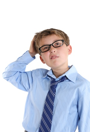 studious: School boy scratches head whilst thinking of an idea or answer or may even be unsure or confused.  White background. Stock Photo