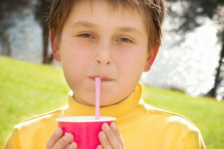 skivvy: A young boy sips strawberry milkshake outdoors.  He is wearing a yellow skivvy and is backlit by the sunshine.  Some texture added.