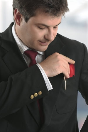 eftpos: A smartly dressed man putting a business card, credit card or other type of  card into his top jacket pocket. Stock Photo