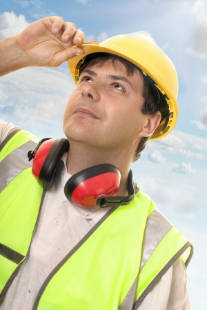 Hard working builder, construction worker or foreman looking up or overseeing progress.  Sunlit sky and clouds background photo