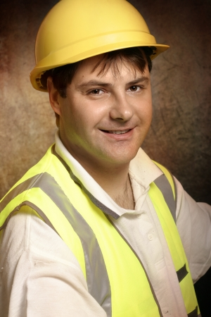 Confident builder, handyman or construction worker wearing hard hat and vest is smiling.   photo