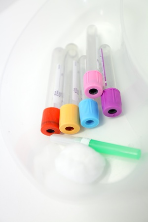 unlabelled: Unlabelled pathology phlebotomy, blood collecting vacutainer tubes a 21 gauge needle and cotton wool lying in a kidney dish for a blood collection procedure