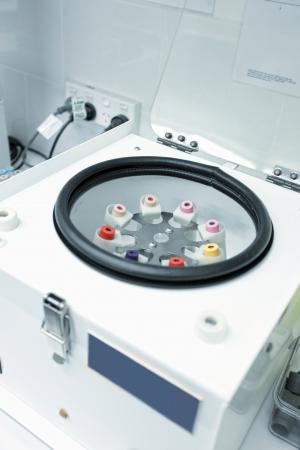 Una centrífuga en la sala de trabajo de laboratorio de un centro de recogida de sangre de patología médica. El cientrifuge está sosteniendo varios tubos, acero inox, EDTA, oligoelementos k2, glucosa, k2 EDTA para hematología bancos de sangre