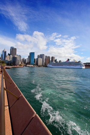 ferries: Sydney, Australia - September 15, 2013:  View of city of Sydney, Sydney Harbour, Circular Quay with Carnival Spirit docked on the west side of the Quay on a sunny Autumn day