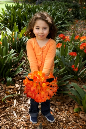 Sweet little girl holding a bunch of clivia miniata  bush lilies  picked from the garden photo