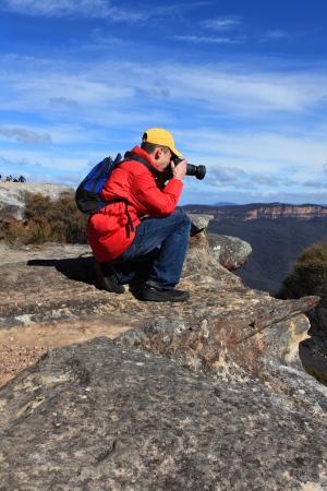 A photographer shoots photos of a scenic mountain landscape  photo