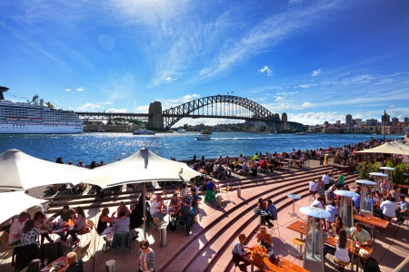 Sydney, Australia - September 15, 2013: Residents and visitors dine, relax and basque in the glorious afternoon sun quayside by the harbour Sydney Australia.  Iconic Circular Quay is a must visit for every tourist. Редакционное