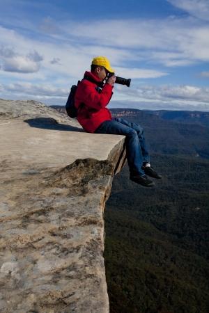 Tourist or photographer on a cliff edge taking photos  of a mountainous landscape photo