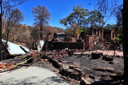 Na de brand. Bosbrand vernietigt huizen en voertuigen in een willekeurig patroon, terwijl sommige zijn volledig gespaard, anderen worden met de grond gelijk.