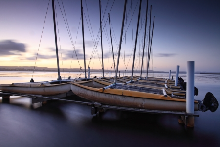 moorings: Catamarans moored on Tuggerah Lakes at Long Jetty, Australia after sundown. Long Exposure with lens filters Stock Photo