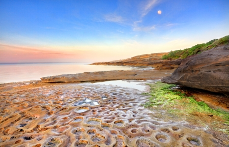 moonscape: Sunrise at Botany Bay, La Perouse, Sydney Australia on a calm summers morning, the moon still shining overhead  of the strange moonscape crater like potholes in the rocks below