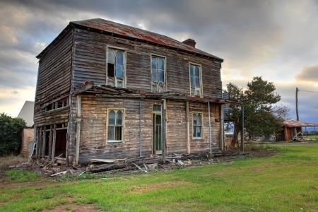 Een vervallen twee verdiepingen laat-Victoriaanse Georgische boerderij met golfplaten dak met zolder en corbelled bakstenen open haard, niet meer leefde in Het had ooit een bovenverdieping veranda met mooie smeedijzeren traliewerk Het ligt tussen de Haw Stockfoto