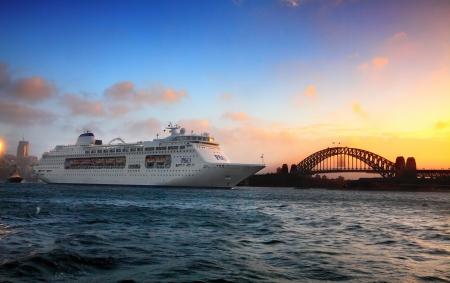 encrespado: Sydney, Australia - 29 de diciembre de 2013; PO crucero navega agitadas aguas del puerto al amanecer por una visi�n recortada de Sydney Harbour Bridge de obturaci�n lenta