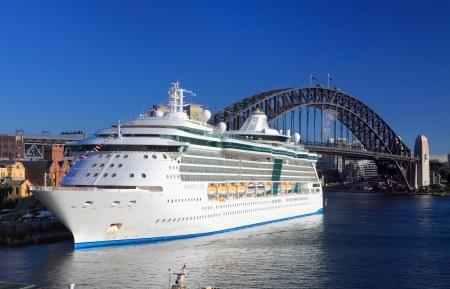 schepen: Sydney, Australië - 1 december 2013; Royal Caribbean Cruises Radiance of the Seas stralend in de haven van Sydney Circular Quay, Harbour Bridge op de achtergrond
