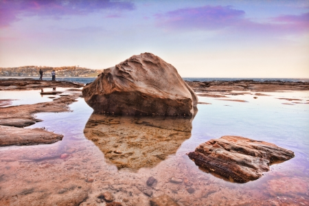obscurity: South Avoca Rocks, late afternoon sunset  Australia.  Larger rocks sit in a large still rockpool at low tide.This is a bracketed shot hdr   People in background have been blurred for obscurity.