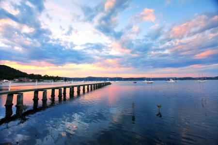 water's edge: Saratoga sunset, jetty wharf and yachts moored at Saratoga on the Central Coast, Australia